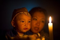 Kyrgyz Baby and Sister in Front of a Candle