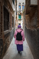 Woman Dressed in Pink and Purple Walks through the Streets of Venice